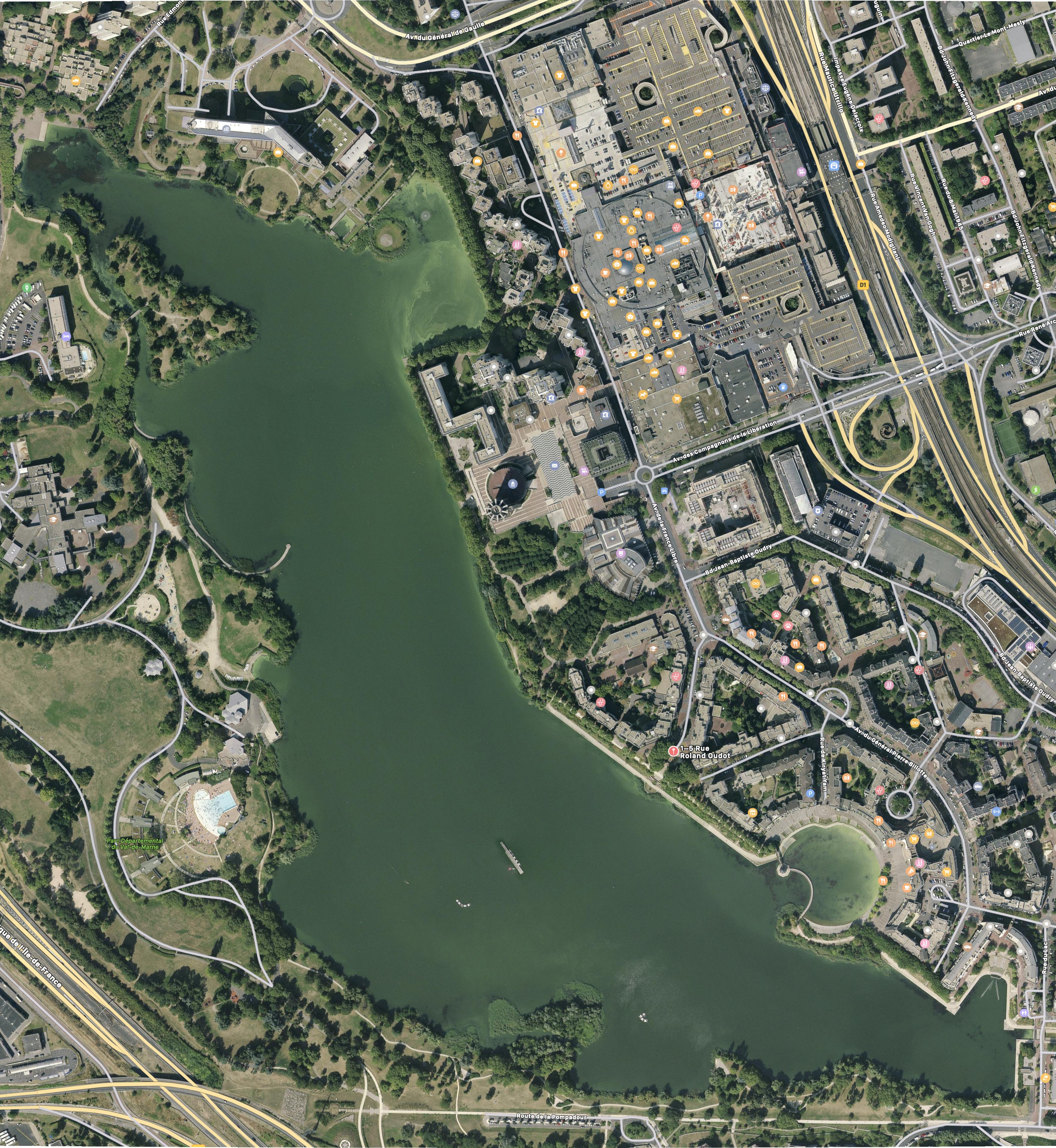 Vue aérienne du lac avec taches vertes.